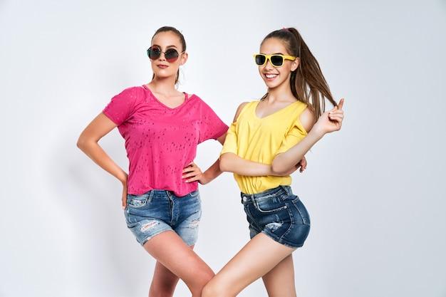 Dwie młode piękne uśmiechnięte hipster międzynarodowych hipster w modne letnie ubrania beztroskie kobiety pozowanie na białym tle