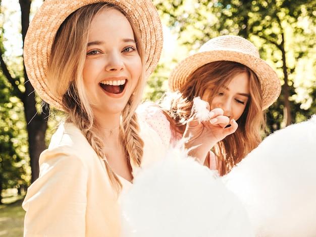 Dwie młode piękne uśmiechnięte hipsterki w modnej letniej sukience