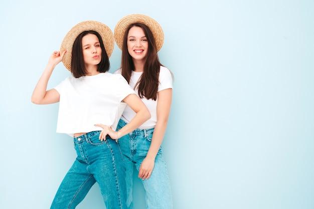 Dwie młode piękne uśmiechnięte hipsterki w modnej, tej samej letniej białej koszulce i dżinsach