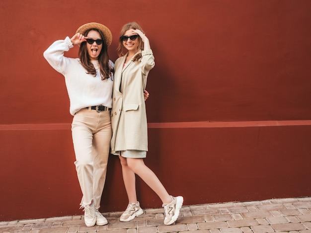 Dwie młode piękne uśmiechnięte hipsterki w modnym białym swetrze i płaszczu