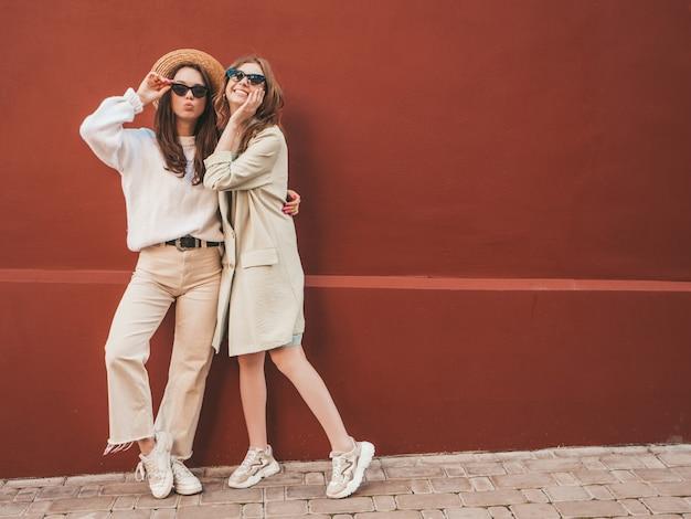 Dwie młode, piękne, uśmiechnięte hipsterki w modnym białym swetrze i płaszczu