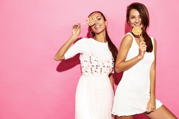 Dwie młode piękne uśmiechnięte kobiety brunetka w modnej letniej sukience ubrania. beztroskie gorące kobiety pozuje blisko menchii ściany. pozytywne śmieszne modele z lollipop