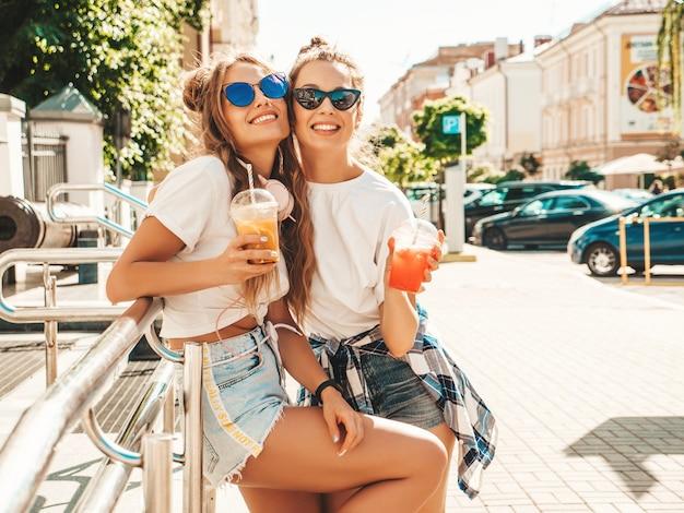 Dwie młode piękne uśmiechnięte kobiety hipster w modnych letnich ubraniach