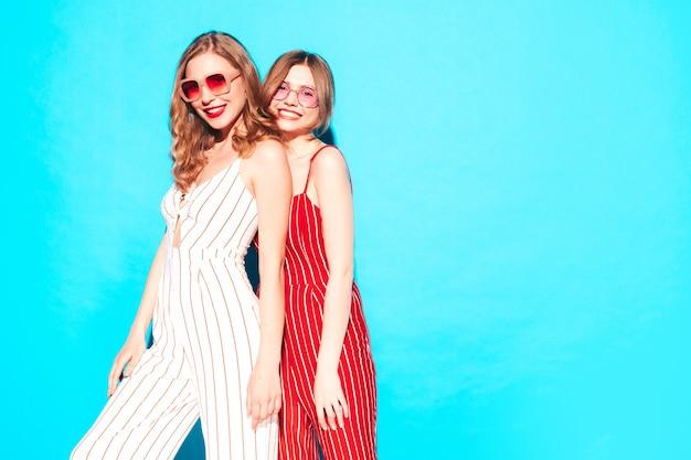 Dwie młode piękne uśmiechnięte kobiety hipster w modnych letnich ubraniach!