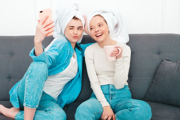 Dwie młode piękne uśmiechnięte kobiety siedzące przy kanapie. beztroskie modelki pozujące w domu w eleganckim mieszkaniu lub pokoju hotelowym