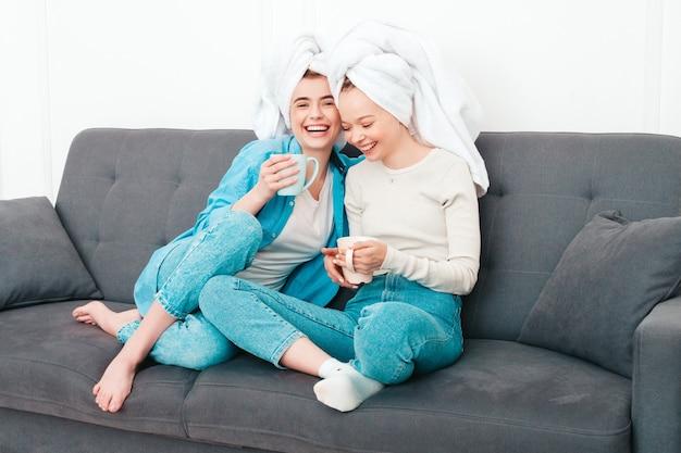 Dwie młode piękne uśmiechnięte kobiety siedzące przy kanapie. beztroskie modelki pozujące we wnętrzach w eleganckim mieszkaniu lub pokoju hotelowym. robią zabiegi kosmetyczne w domu?