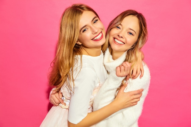 Dwie młode piękne uśmiechnięte kobiety w modne lato białe ubrania