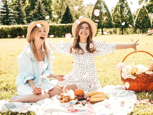Dwie młode piękne uśmiechnięte kobiety w modnej letniej sukience i kapeluszach. beztroskie kobiety robią piknik na zewnątrz.