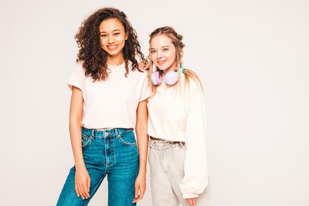 Dwie młode piękne uśmiechnięte międzynarodowych hipster kobieta w modne letnie ubrania. beztroskie kobiety pozują w studio