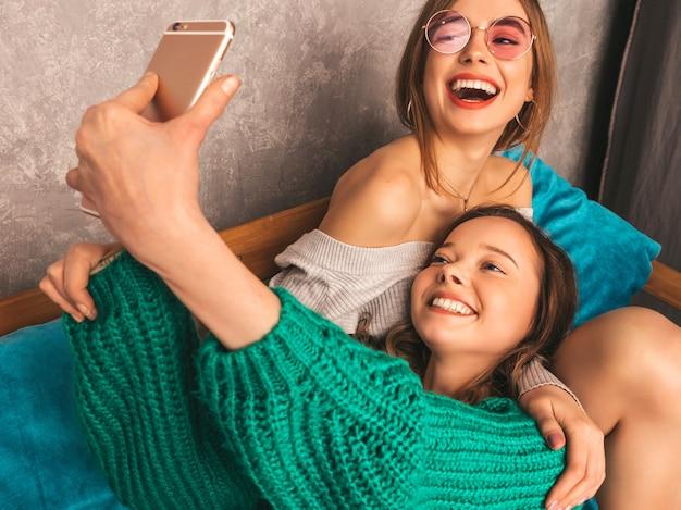 Dwie młode piękne uśmiechnięte wspaniałe dziewczyny w modne letnie ubrania. seksowne beztroskie kobiety pozuje w wnętrzu i bierze selfie. pozytywne modele zabawy ze smartfonem.