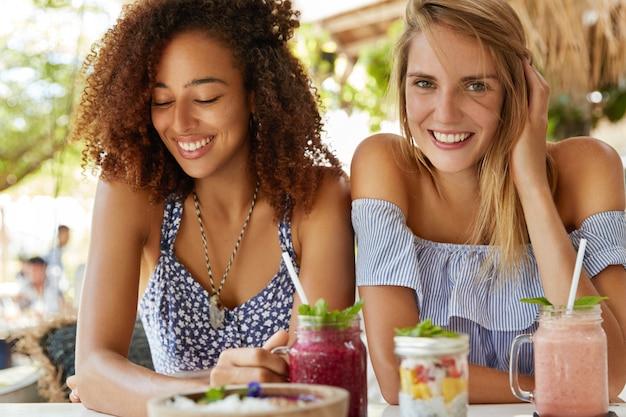 Dwie młode, przyjacielskie suczki ubrane w letnie stroje pozytywnie się uśmiechają, jedzą egzotyczne desery i piją smoothie, cieszą się chwilą wypoczynku na tarasie kawiarnianym wnętrzu, będąc w dobrym nastroju.