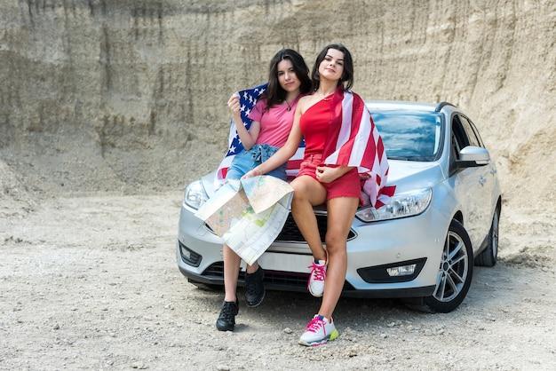 Dwie młode przyjaciółki patrzą na mapę w pobliżu swojego samochodu i cieszą się letnią wycieczką samochodem