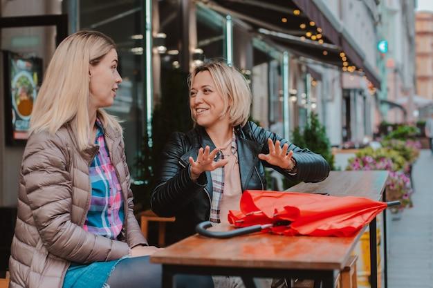 Dwie młode przyjaciółki spotkały się w miejskiej kawiarni i bawią się na czacie.