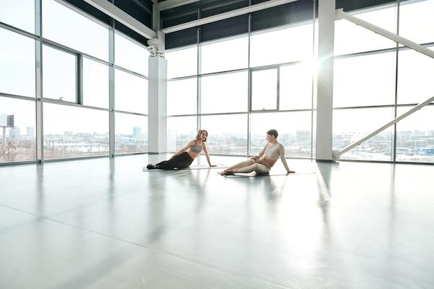 Dwie młode przyjazne sportsmenki w aktywnych ubraniach siedzą na matach po treningu i rozmawiają z dużymi oknami w centrum rekreacji