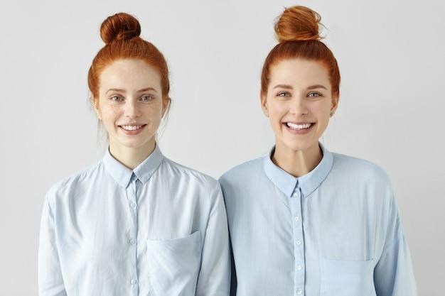 Dwie młode rudowłose kobiety rasy kaukaskiej wyglądające podobnie, ubrane w te same formalne jasnoniebieskie koszule