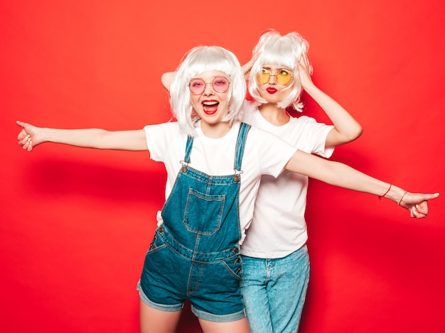 Dwie młode seksowne hipster dziewczyny w białych perukach i czerwonych ustach. piękne modne kobiety w letnich ubraniach. bezpłatne modele pozowanie w pobliżu czerwonej ściany w studio lato w okularach przeciwsłonecznych