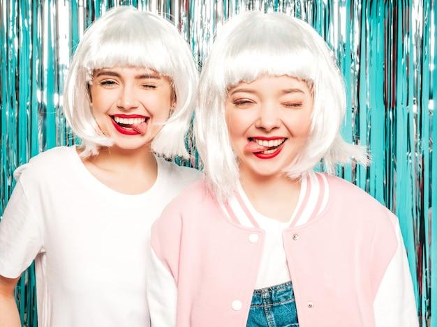 Dwie młode seksowne hipster dziewczyny w białych perukach i czerwonych ustach. piękne modne kobiety w letnie ubrania letnie pokazuje język