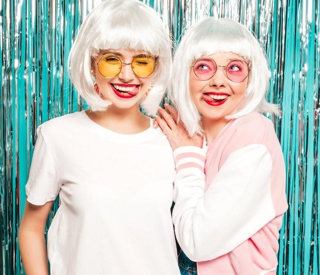 Dwie młode seksowne hipster dziewczyny w białych perukach i czerwonych ustach. piękne modne kobiety w letnie ubrania letnie w okularach przeciwsłonecznych