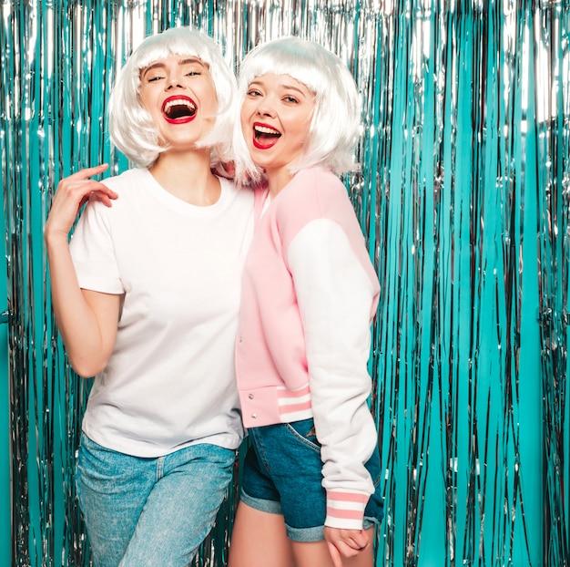 Dwie młode seksowne hipster dziewczyny w białych perukach i czerwonych ustach. piękne modne kobiety w letnie ubrania letnie zabawy