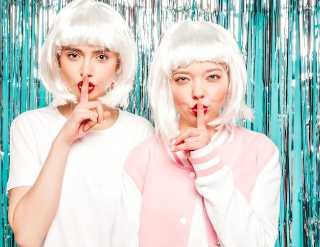 Dwie młode seksowne hipster dziewczyny w białych perukach i czerwonych ustach. piękne modne kobiety w letnie ubrania. modele pozowanie na niebieskim srebrnym tle błyszczący blichtr w studio. pokazuje cisza palec cisza znak, gest