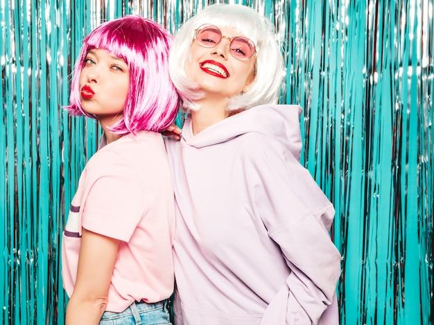 Dwie młode seksowne hipster dziewczyny w peruki i czerwone usta. piękne modne kobiety w letnie ubrania zabawy