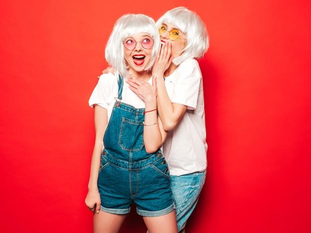 Dwie młode seksowne hipsterki w białych perukach i czerwonych ustach. piękne modne kobiety w letnich ubraniach. beztroskie modele pozujące w pobliżu czerwonej ściany w letnim studio dzieli tajemnicę, plotki