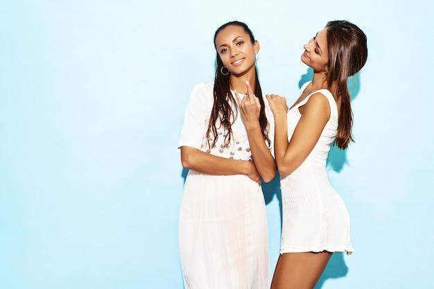Dwie młode seksowne piękne uśmiechnięte hipster kobiety w modne letnie ubrania. gorące beztroskie kobiety pozuje blisko błękit ściany. pozytywne modele