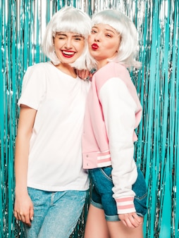 Dwie młode seksowne uśmiechnięte dziewczyny hipster w białe peruki i czerwone usta. piękne modne kobiety w letnie ubrania lato