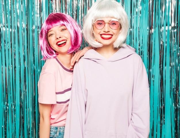 Dwie młode seksowne uśmiechnięte dziewczyny hipster w białe peruki i czerwone usta. piękne modne kobiety w letnie ubrania