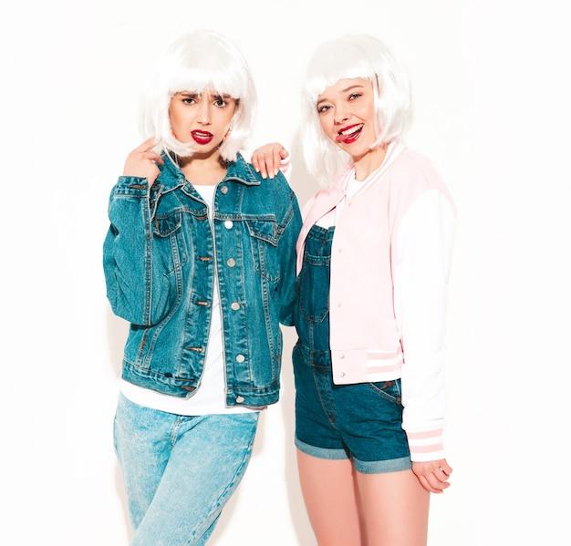 Dwie młode seksowne uśmiechnięte hipster dziewczyny w białych perukach i czerwone usta wariują
