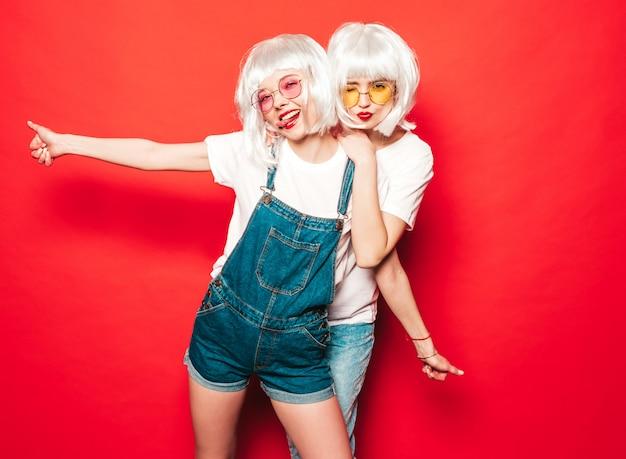 Dwie młode seksowne uśmiechnięte hipster dziewczyny w białych perukach i czerwonych ustach. piękne modne kobiety w letnie ubrania. bezpłatne modele pozowanie w pobliżu czerwonej ściany w studio lato w okularach przeciwsłonecznych