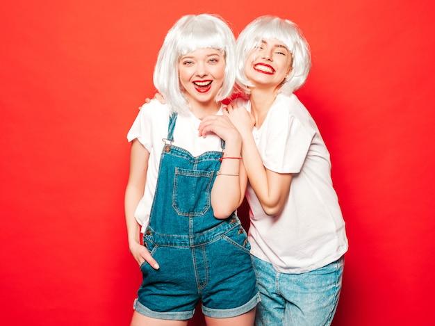 Dwie młode seksowne uśmiechnięte hipster dziewczyny w białych perukach i czerwonych ustach. piękne modne kobiety w letnie ubrania. beztroskie modele pozowanie w pobliżu czerwonej ściany w studio lato szaleje