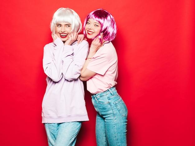 Dwie młode seksowne uśmiechnięte hipster dziewczyny w białych perukach i czerwonych ustach. piękne modne kobiety w letnie ubrania. beztroskie modele pozowanie w pobliżu czerwonej ściany w studio wariuje