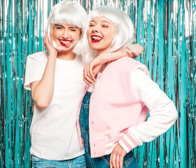 Dwie młode seksowne uśmiechnięte hipster dziewczyny w białych perukach i czerwonych ustach. piękne modne kobiety w letnie ubrania. pokazują języki