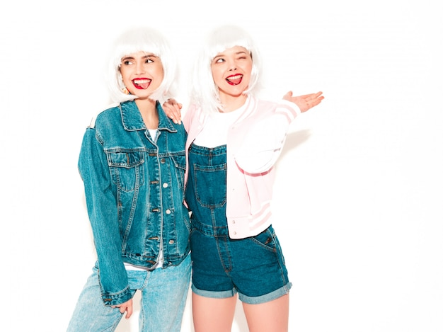 Dwie młode seksowne uśmiechnięte hipster dziewczyny w białych perukach i czerwonych wargach lat wariują