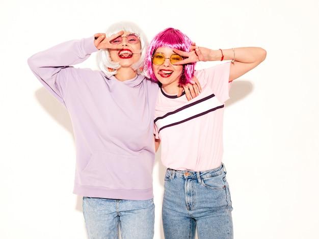 Dwie młode seksowne uśmiechnięte hipster dziewczyny w perukach i czerwone usta. piękne modne kobiety w letnie ubrania. beztroskie modele pozowanie w pobliżu białej ściany w studio wariuje i przytulanie