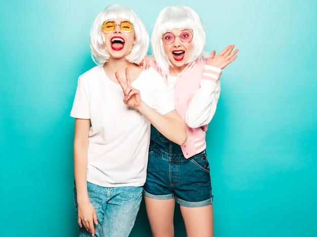 Dwie młode seksowne uśmiechnięte hipster dziewczyny w perukach i czerwone usta. piękne modne kobiety w letnie ubrania. modele wolne od pozowanie blisko niebieskiej ściany w studio lato zszokowany i zaskoczony