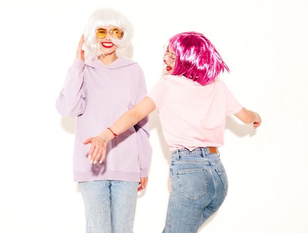 Dwie młode seksowne uśmiechnięte hipster dziewczyny w perukach i czerwone usta. piękne modne kobiety w ubraniach. modele wolne od pozowanie blisko białej ściany w studio wariuje i tańczy