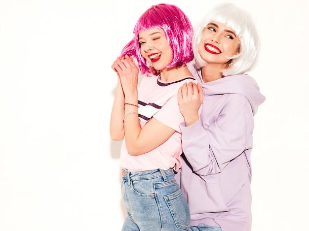 Dwie młode seksowne uśmiechnięte hipster dziewczyny w perukach i czerwone usta. piękne modne kobiety w ubraniach. modele wolne od pozowanie blisko białej ściany w studio wariuje i tulenie