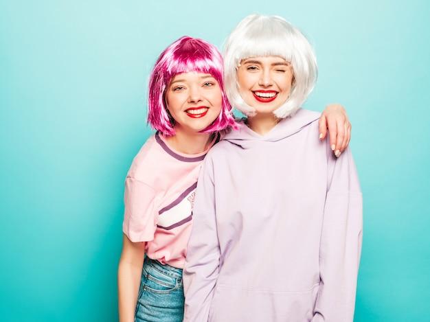 Dwie młode seksowne uśmiechnięte hipster dziewczyny w peruki i czerwone usta. piękne modne kobiety w letnie ubrania. modele bez szwu pozowanie w pobliżu niebieską ścianą w studio