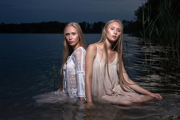 Dwie młode siostry bliźniaczki o długich blond włosach pozują w lekkich sukienkach w wodzie jeziora w letnią noc. wieczorna sesja plenerowa