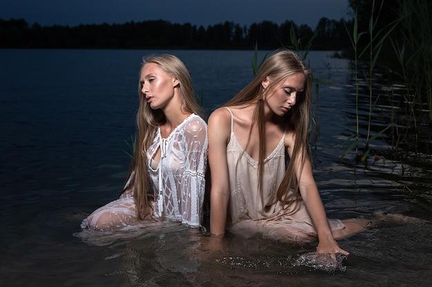 Dwie młode siostry bliźniaczki pozują w lekkich sukienkach w wodzie jeziora w letnią noc