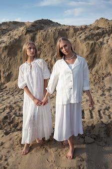 Dwie młode siostry bliźniaczki pozujące w pustynnym lub piaskowym kamieniołomie w eleganckich białych ubraniach