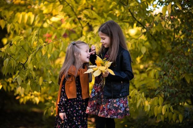 Dwie młode siostry w jesiennych sukienkach, skórzanej kurtce i czerwonym swetrze pozują w jesiennym parku