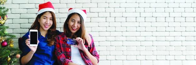 Dwie młode śliczne kobiety trzyma smartphone i kredytową kartę dla robić zakupy online