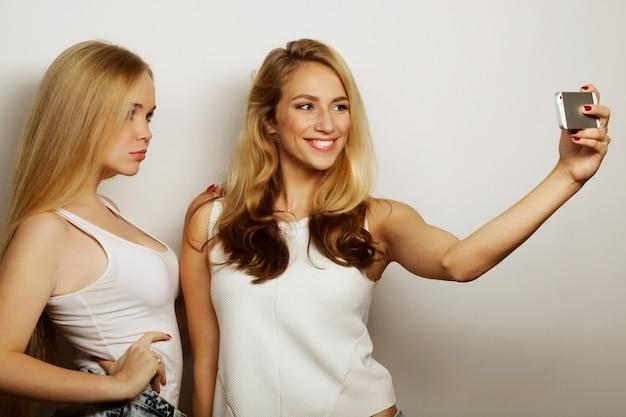 Dwie młode śmieszne kobiety robiące selfie z telefonem komórkowym