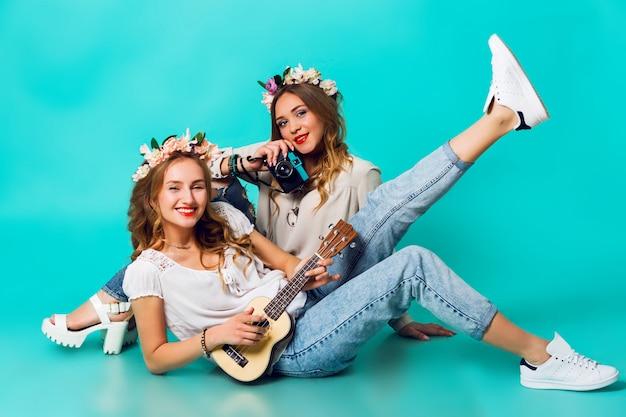 Dwie młode śmieszne modne dziewczyny pozują na tle niebieskiej ściany w letnim stroju z wieńcem kwiatów w dżinsach i paczce boho. .