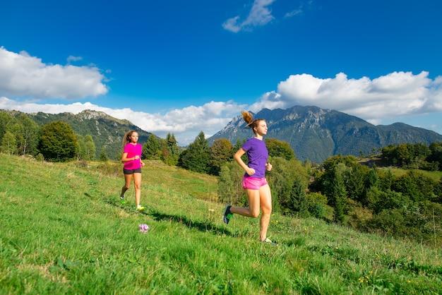Dwie młode sportowe dziewczyny biegają razem na trawie w górskiej scenerii - jogging w naturze.