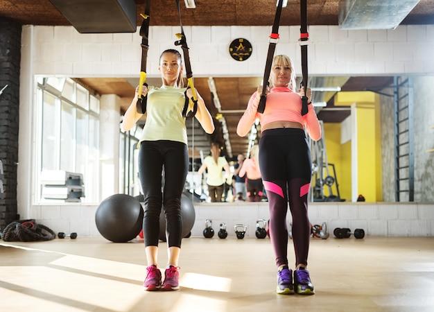 Dwie młode sprawne dziewczyny na siłowni wykonujące trening zawieszenia trx.