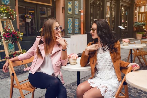 Dwie młode stylowe kobiety siedzą w kawiarni